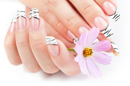 Hands with striped manicure relaxing with flowers