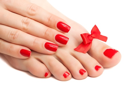 manicure and pedicure: Red manicure and pedicure with a bow  isolated