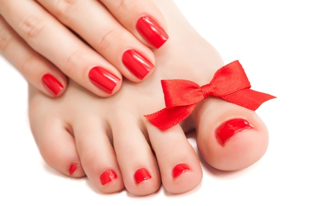 nail care: Red manicure and pedicure with a bow  isolated