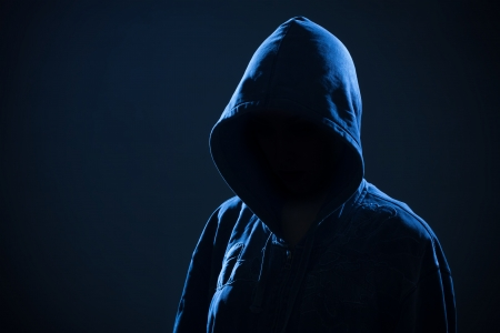 Scary woman with hood in darkness
