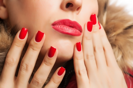 part of the girl s face with red lips and manicure photo