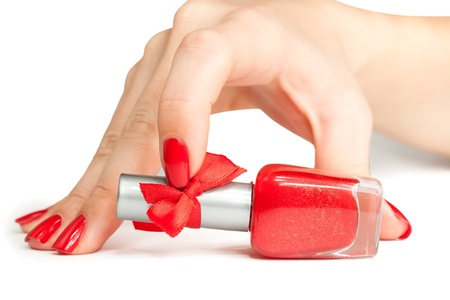 woman s hand with a bottle of red nail polish photo