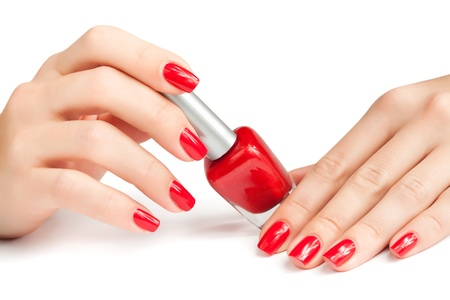 polish: Hands with red manicure and nail polish bottle isolated Stock Photo