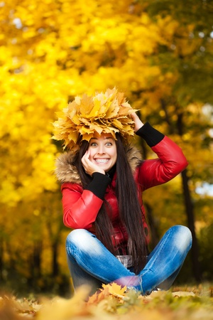 pretty woman in a wreath of autumn leaves photo