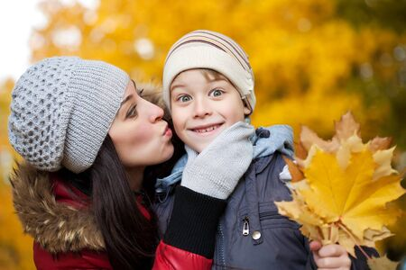 happy Mom is kissing her son in a yellow autumn park Stock Photo - 17540486