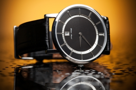 luxury watches with a leather strap on the orange background photo