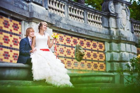bride and groom are sitting near the patterned wall photo