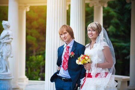 happy bride and groom near white column photo