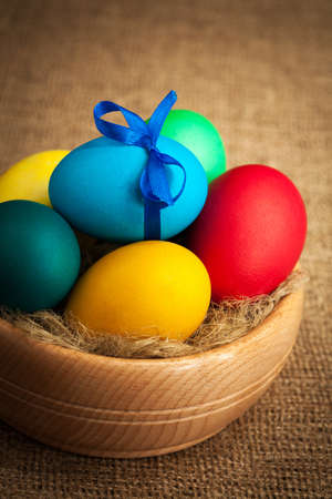 wooden bowl with colored Easter eggs photo