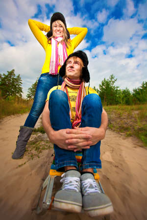 Funny couple are sledding at summer photo