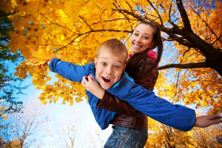 happy mom and son are playing in the autumn park