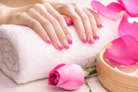 nail care: female hands with fragrant rose petals and towel
