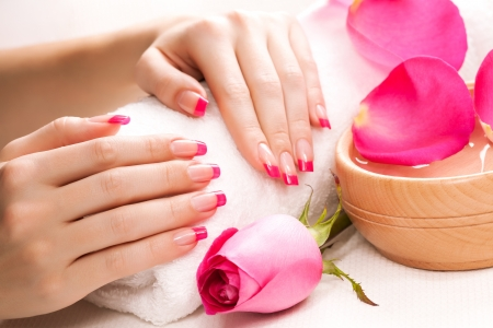 female hands with rose petals and towel  Spa