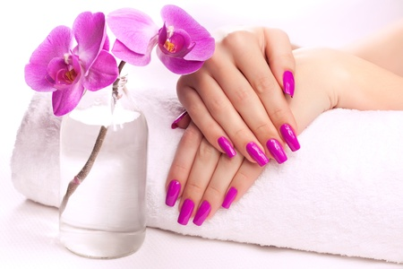 nail care: female hands with fragrant orchid and towel  Spa