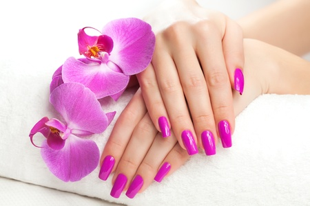 female hands with fragrant orchid and towel  Spa