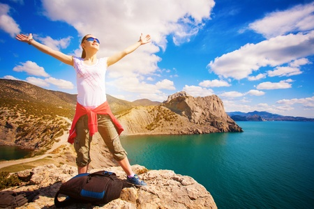 woman tourist is enjoying landscape with outstretched arms photo