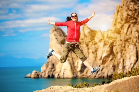 young woman is jumping over mountain peak photo
