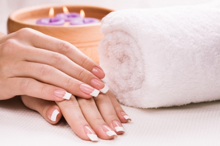beauty spa: female hands with aromatic candles and towel  Spa