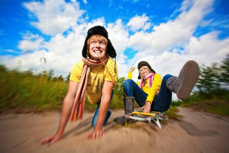 crazy boy and girl are sledding at summer photo