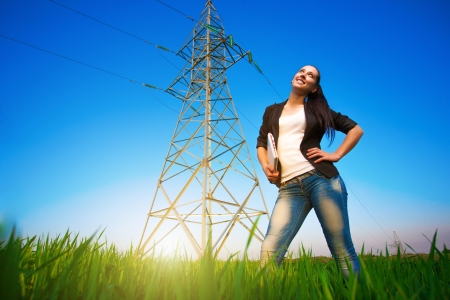 pretty businesswoman in a field with a laptop  power lines photo