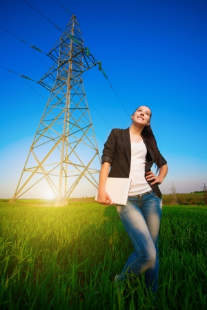 cute woman in a green field with a laptop  power lines photo