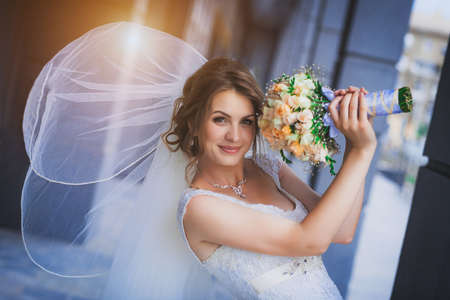 gals: bride against a blue modern building background
