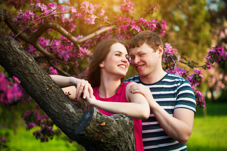 he she: loving couple are hugging on the apple orchard