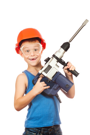 assistant engineer: kid in a helmet with electric hammer Stock Photo