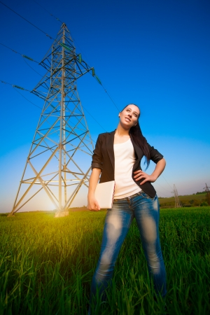 happy businesswoman in a green field with a laptop. power lines photo