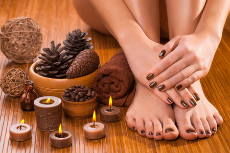beautiful brown manicure and pedicure on the white photo