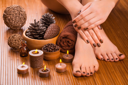 manicure and pedicure: beautiful brown manicure and pedicure on the bamboo Stock Photo