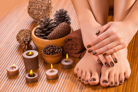 beautiful brown manicure and pedicure on the bamboo photo