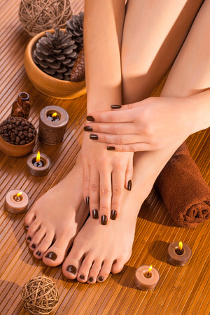 spa pedicure: beautiful brown manicure and pedicure on the bamboo Stock Photo