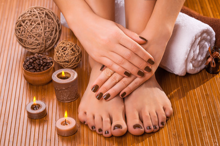 pedicure: beautiful brown manicure and pedicure on the bamboo Stock Photo