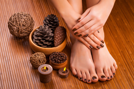 beautiful brown manicure and pedicure on the bamboo Stockfoto