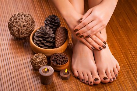 beautiful brown manicure and pedicure on the bamboo Standard-Bild