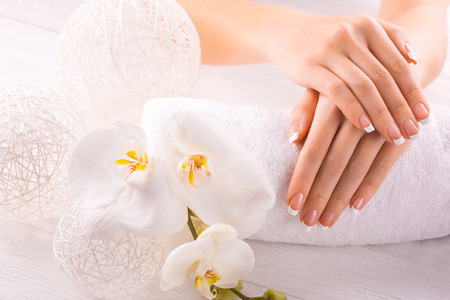 Woman hands with white orchid on a towel photo