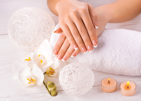 Beautiful hands with manicure and orchid flower photo