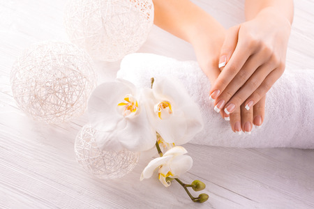 Woman hands with white orchid on a towel