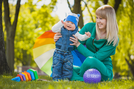 fondness: Happy mother and baby playing on meadow Stock Photo