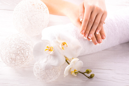Beautiful hands with manicure and orchid flower Standard-Bild