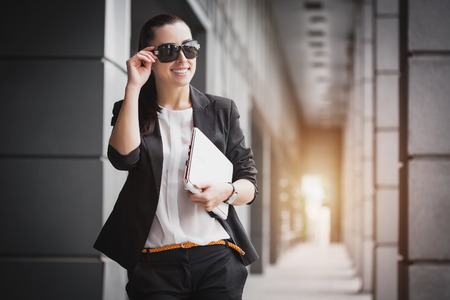 Femme d'affaires prospère avec un ordinateur portable. Ville d'affaires travaillant.