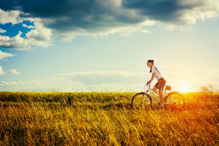 ライフスタイル: 若い女性は健康的なライフ スタイル外の自転車に乗る