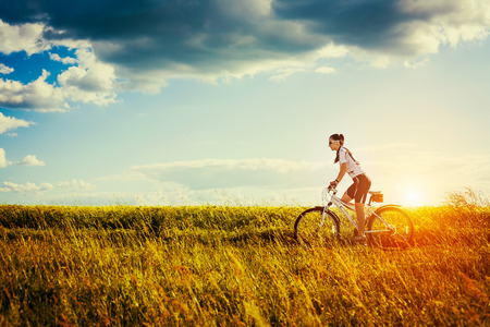 âhealthy: Mujer joven que está montando la bicicleta fuera de Estilo de Vida Saludable Foto de archivo