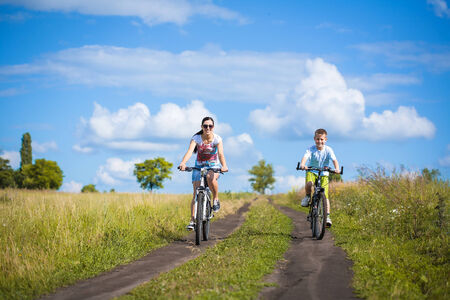 Happy family  mother and son riding  in the field Stock Photo