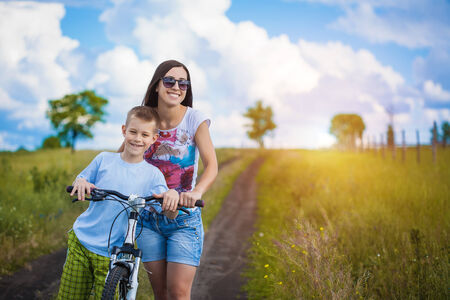 velo: Happy family  mother and son riding bicycle in the field Stock Photo