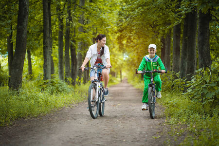 Happy family  mother and son riding bicycle in the park Stock Photo