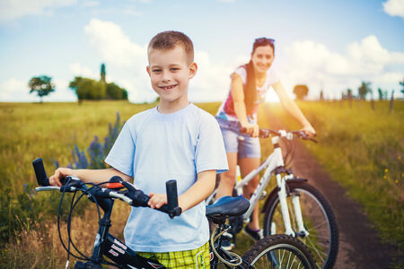 Happy family  mother and son riding bicycle in the field Stock Photo