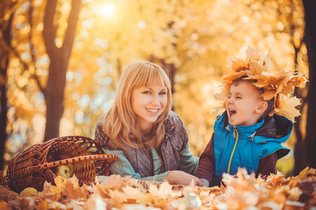 mother and her kid have fun in the yellow leaves photo