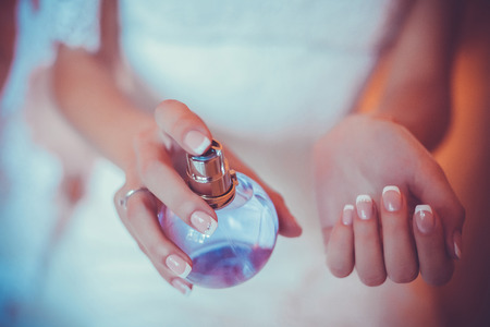 bride applying perfume on her wrist Stock Photo